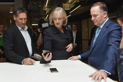 Vodafone CEO Russell Stanners, Communications Minister Amy Adams and Prime Minister John Key try a new smartphone charger during the opening of the InnoV8 building in Christchurch's Innovation Precinct.