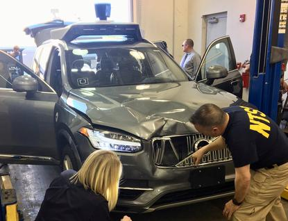 U.S. National Transportation Safety Board (NTSB) investigators examine a self-driving Uber vehicle involved in a fatal accident in Tempe, Arizona, U.S., March 20, 2018. National Transportation Safety Board