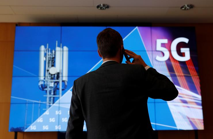 An employee of Germany's Federal Network Agency (Bundesnetzagentur) uses his mobile phone in front of a screen set up for the auction of spectrum for 5G services at the Bundesnetzagentur headquarters in Mainz, Germany, March 18, 2019. REUTERS/Kai Pfaffenbach