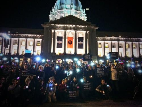 Dozens of protestors in favor of strong net neutrality rules gather in front of San Francisco's City Hall late Thursday.