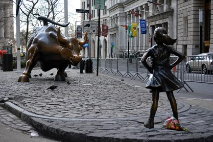 `The Fearless Girl` statue facing the Charging Bull on Wall Street.