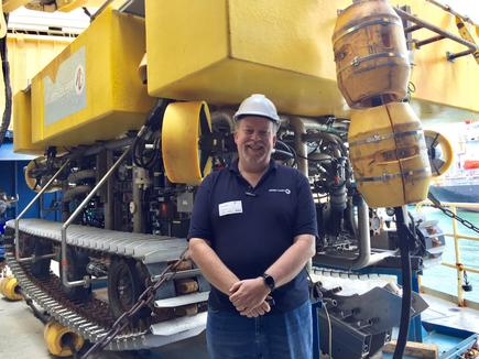 Steven Onley of Alcatel Lucent in front of the ship's remotely operated vehicle