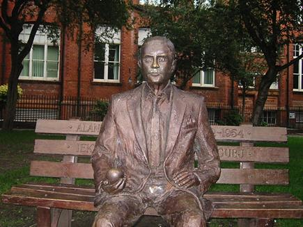 A statue of Turing sits on a bench in Sackville Park, Manchester, England.