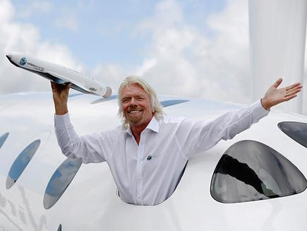 Entrepreneur Richard Branson waves a model of a LauncherOne cargo spacecraft from a window of an actual size model of SpaceShipTwo on display, after Virgin Galactic's LauncherOne announcement in 2012.