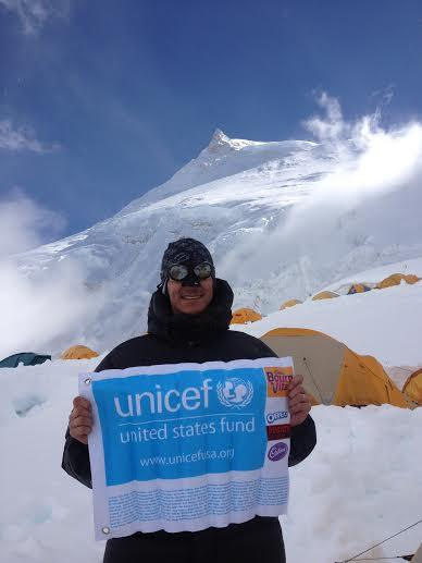 Marcelo De Santis in a camp in Manaslu, showing the flag with the names of supporters to the campaign.