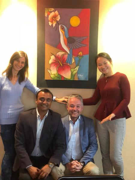 Stephen Lawrence with the other IBM'er team members in Ecuador:  Vania Doria of Brazil,  Vikram Tiwari of India; and Lilian Wu of  China. On the background is an artwork they bought for their client SENDAS, featuring the national bird of Ecuador, the hummingbird (photo taken from Stephen's blog)